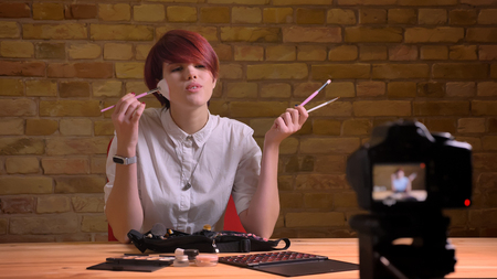 Closeup shoot of young attractive hipster female video vlogger streaming live and advertising makeup while talking on camera in apartment