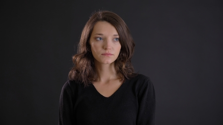 Portrait of fragile young brunette woman watching thoughtfully leftwards on black background.