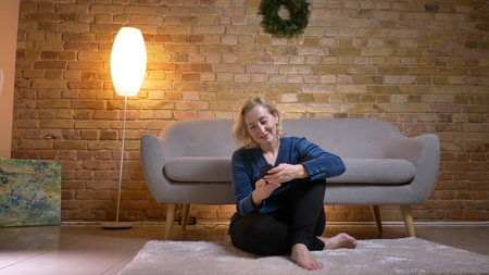 Portrait of joyful senior caucasian lady sitting on floor and watching into smartphone happily in cozy home atmosphere.