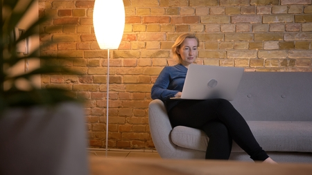 Portrait in profile of senior caucasian woman sitting on sofa and working with laptop attentively in cozy home atmosphere. Stock Photo