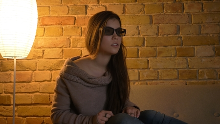 Closeup portrait of young attractive caucasian female watching a movie on TV in 3D glasses with excited facial expression