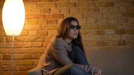 Closeup portrait of young cute caucasian female watching a movie on TV in 3D glasses being shocked and excited