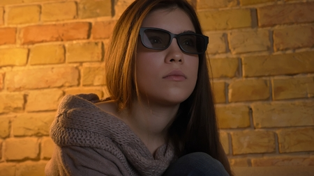 Closeup portrait of young attractive caucasian female face watching a movie on TV in 3D glasses with curious facial expression