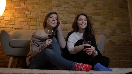 Closeup portrait of two young pretty women watching TV and chilling with wine while sitting on the floor and laughing happily in a cozy apartment indoors 写真素材