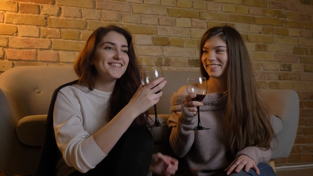 Closeup portrait of two young pretty women watching a movie TV chilling with wine laughing cheerfully sitting on the floor in a cozy apartment indoors