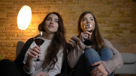 Closeup bottom up portrait of two young pretty women watching a TV show drinking wine in a cozy apartment indoors