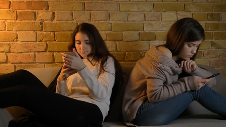 Closeup portrait of two young pretty caucasian girls browsing on the phones while resting on the couch indoors in a cozy apartment