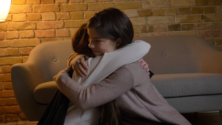 Closeup portrait of two young pretty caucasian girls hugging with love indoors in a cozy apartment