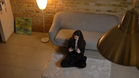 Closeup top view portrait of young pretty caucasian female texting on the tablet in a cozy home indoors