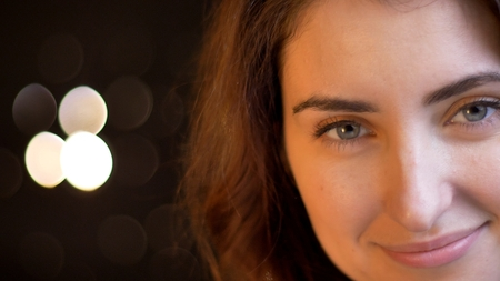 Closeup shoot of young attractive caucasian female face smiling and being joyful looking at camera with bokeh background