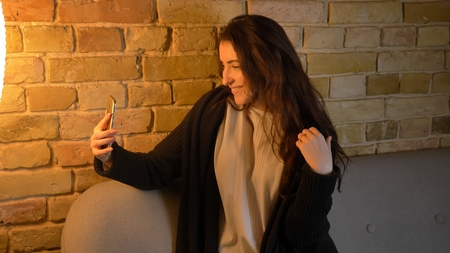 Closeup shoot of young pretty caucasian brunette female taking selfies on the phone posing in front of the camera while sitting on the couch indoors in a cozy apartment