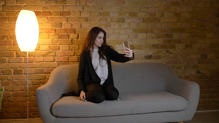 Closeup shoot of young pretty caucasian brunette female taking pictures on the phone sitting on the couch indoors in a cozy apartment