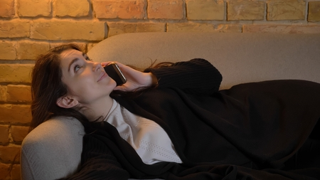 Closeup shoot of young pretty caucasian brunette female lying on the couch and having casual conversation on the phone indoors in a cozy apartment