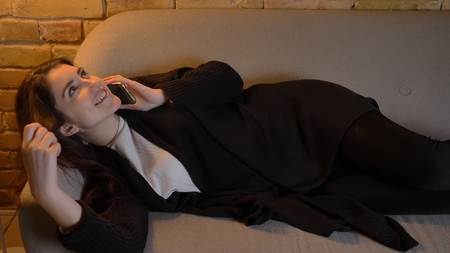 Closeup shoot of young pretty caucasian brunette female lying on the couch and calling on the phone indoors in a cozy apartment
