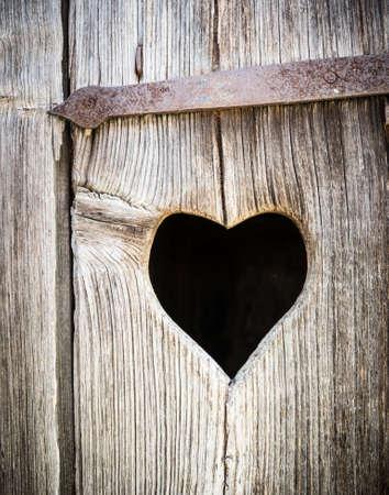 wooden heart at an antique restroom-door