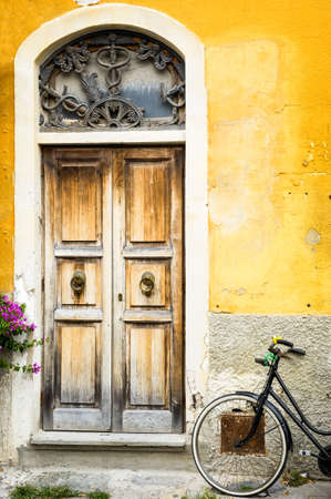 old wooden door and a bike at a house in italy  tuscany  Zdjęcie Seryjne