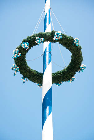 typical bavarian maypole in front of blue sky photo