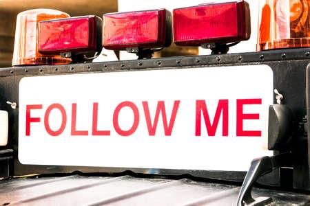 follow me  sign at a car photo