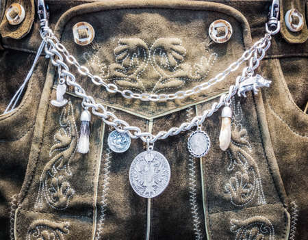 close-up von einem typisch bayerischen Krachlederne - traditionelle Kleidung mit antiken Münzen