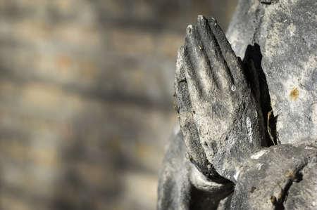 manos orando: las manos juntas de una estatua antigua Foto de archivo