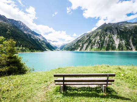 old wooden bench at a lake in austria (zillertal)