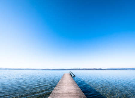 cielo despejado: viejo muelle de madera en un lago
