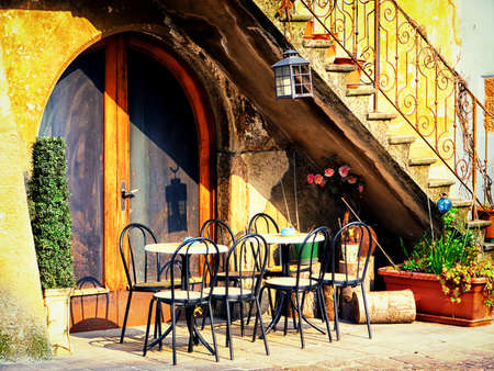 old building facade: tables and chairs at a bistro in italy Stock Photo