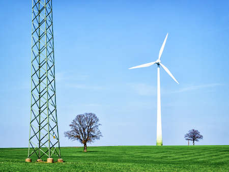 modern wind generator in front of blue sky photo
