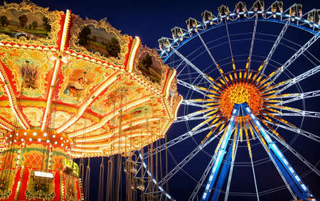ferris wheel: famous ferris wheel and old carousel at the oktoberfest in munich - germany