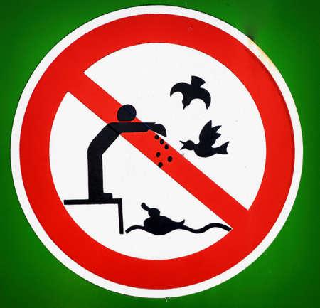 no bird feeding sign at a lake