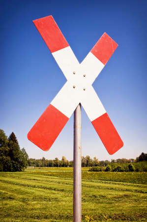 railroad crossing: railroad crossing sign in front of blue sky