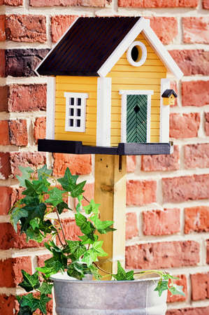 beautiful bird house in fron of brick wall photo