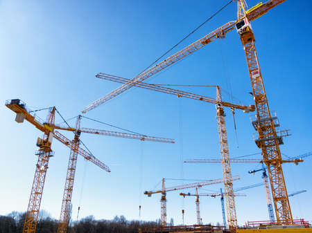 the clear sky: modern construction cranes in front of blue sky