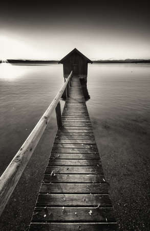 black and white photography: old wooden boathouse at a lake