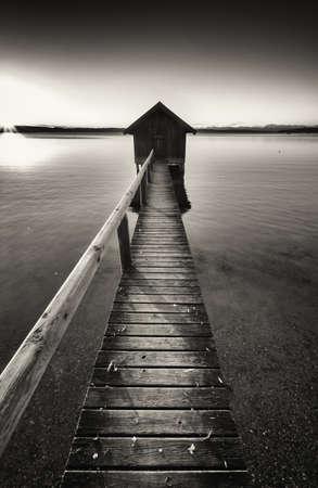 fondo blanco y negro: viejo cobertizo de madera en un lago Foto de archivo