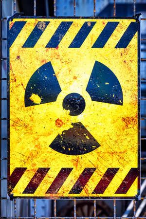 hazardous waste: old nuclear warning sign at a fence