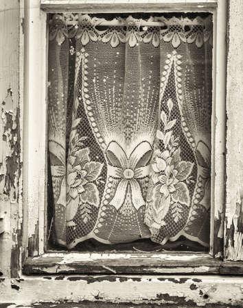 rundown: old curtains at a rundown window Stock Photo