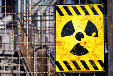 radioactive sign: old nuclear warning sign at a fence