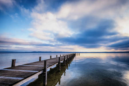 calm water: old wooden jetty at the chiemsee lake in bavaria
