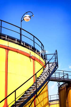 storage tanks: yellow modern storage tanks in front of blue sky