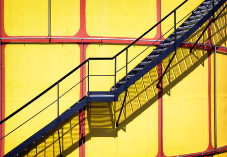 emergency stair: yellow modern storage tanks in front of blue sky