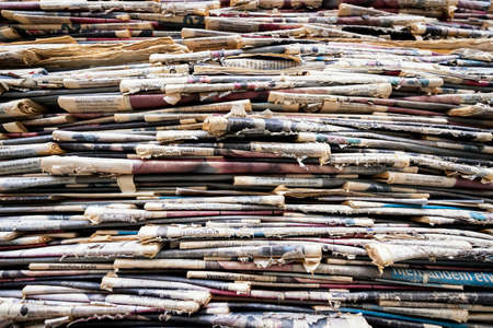 disarrangement: tower of old weathered newspapers