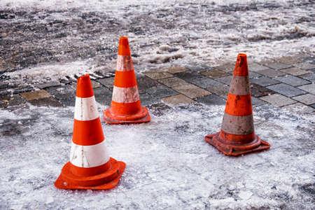traffic cone: traffic cone at a sidewalk in winter Stock Photo