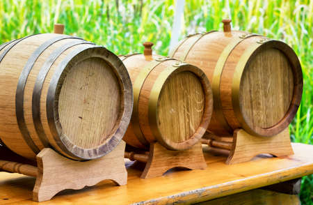 casks: old wooden oil casks in a row Stock Photo