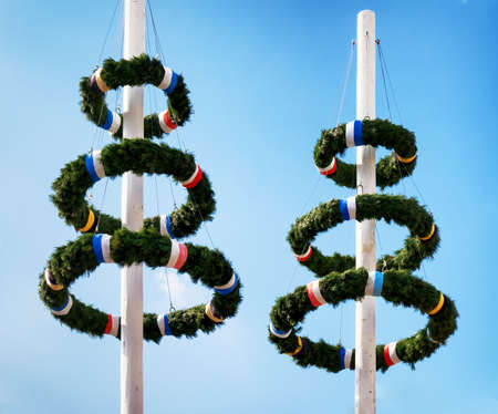 german culture: typical bavarian maypole in front of blue sky