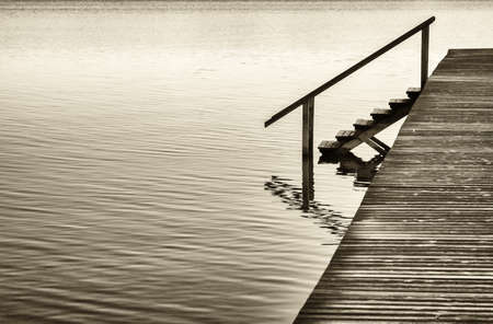 old fashioned sepia: old wooden jetty at the chiemsee lake in bavaria