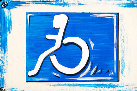 disabled sign: old disabled sign at a wall