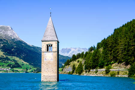 the sunken: famous historic bell tower at the reschenpass - italy