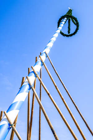 traditonal: typical bavarian maypole in front of blue sky