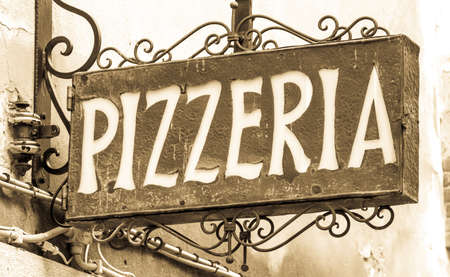 old pizzeria sign at a wall